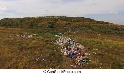 garbage is dropped in front of the hill - a large pile of...