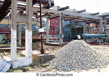 A large pile of rubble, stones on the construction site for the construction of an oil refinery at an oil refinery, a petrochemical plant.