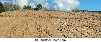 A large pile of sand on a autumn forest construction site. Panoramic collage