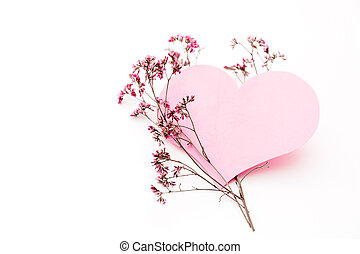 A large pink heart with a place for text decorated with small pink flowers on a white background