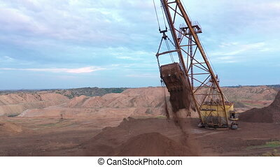 A large old quarry excavator removes the top layer of soil for the extraction of minerals, ores and other minerals.