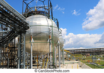 A large round ball-shaped shiny metallic high-pressure iron storage tank for ammonia is strong with pipes and equipment at the petrochemical chemical refinery industrial refinery