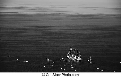 A large sailboat, bark goes into the sea surrounded by many ...