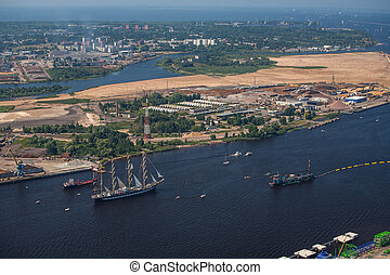 A large sailboat goes along the water area of the Daugava ...