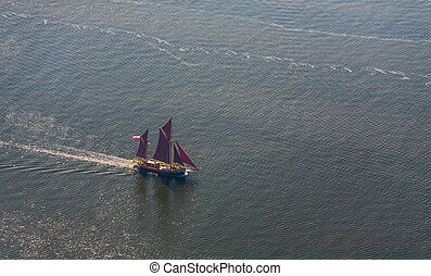 A large sailboat goes to sea under sail. View from above. - ...