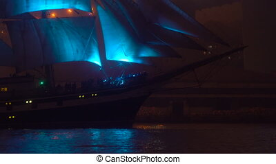 A large sailing vessel with blue illumination sails swims along the harbor. The concept of large human endeavors and aspirations.