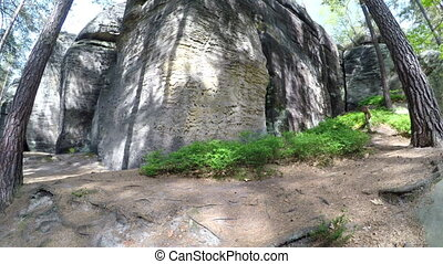 A large sandstone rocks in forest against a sky with...