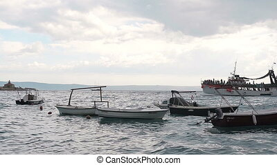 A large ship filled with people floating in the open sea and showing people the coast of Makarska