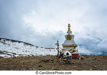 A large stone stupa on the background of the cloudy sky,...