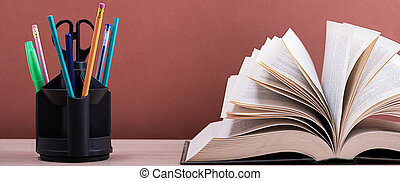 A large thick book with the pages spread out like a fan and a stand with pens, pencils and scissors on the table on a brown background.