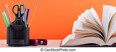 A large thick book with the pages spread out like a fan and a stand with pens, pencils and scissors on the table on a orange background.