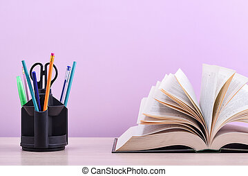 A large thick book with the pages spread out like a fan and a stand with pens, pencils and scissors on the table on a lilac background.