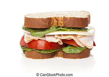 A large turkey sandwhich with tomatoes, cheese, and lettuce