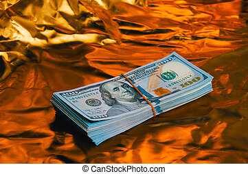 A large wad of dollars on a golden background.