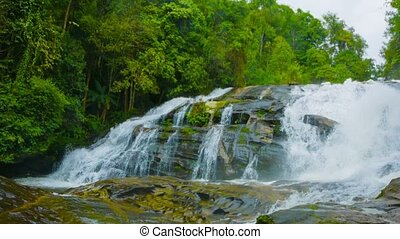 A large waterfall on the river in the forest. Thailand