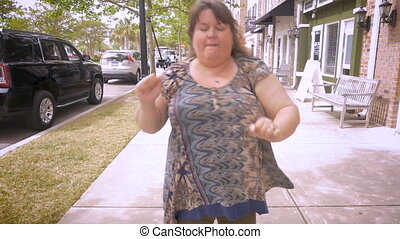 A large woman jammin out celebrating that she won something in slow motion