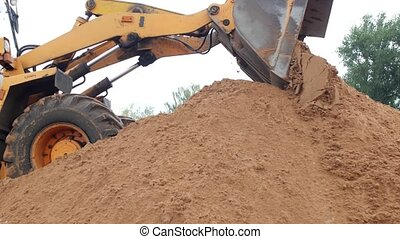 A large yellow loader pours out a bucket of earth, ground...