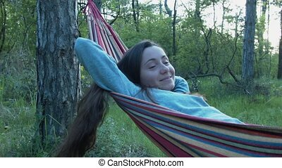 A laughing girl is rocking in a hammock. Portrait of a resting young woman outside the city. Happy leisure in nature.