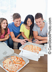 A laughing group of friends gathered around some pizza