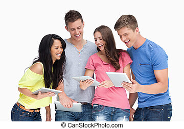 A laughing group of friends looking at their tablet pc's