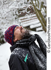 laughing man is outside in the snow