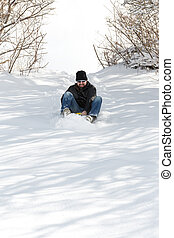 laughing man sledging in deep snow, concept winter and sleigh ride