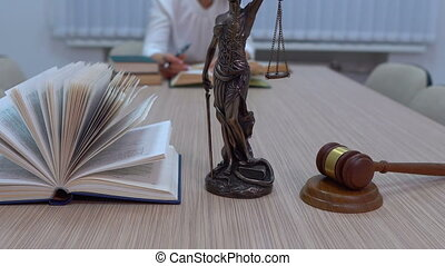 a lawyer in the workplace examines documents and...