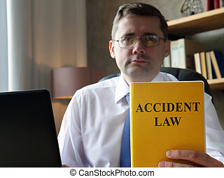 A Lawyer shows a book accident law.