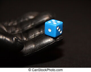 A leather-gloved hand with a dice.