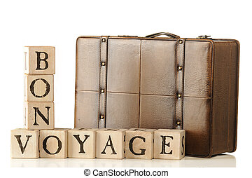 """A leather suitcase sitting behind rustic alphabet blocks that are arranged to say, """"Bon Voyage."""" Isolated on white."""