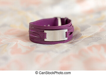 A leather wrist cuff with metal insertions