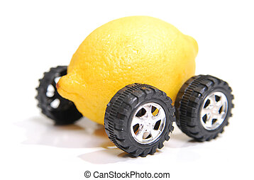 A lemon with wheels representing a defective vehicle. Shallow depth of field focus on fron wheel and front of lemon.