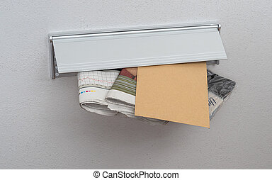 A letter and newspapers in a mail slot