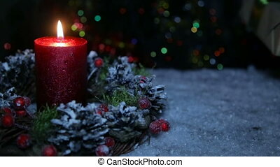 A lighted candle and a gift box on the background of a bokeh