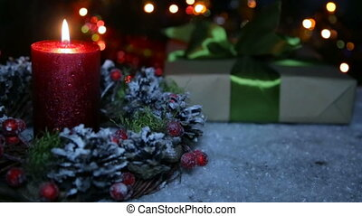 A lighted candle and a gift box on the background of a bokeh...