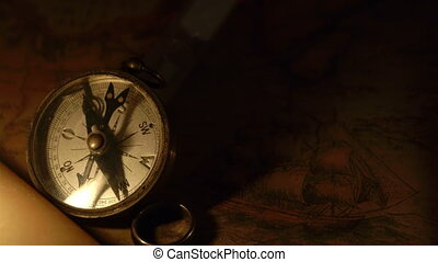 A lighted candle beside a compass