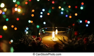 A lighted candle on a Christmas night against the backdrop of a bokeh