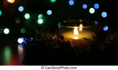 A lighted candle on a Christmas night against the backdrop...
