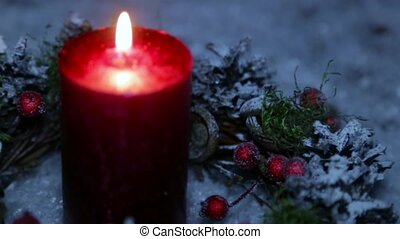 A lighted candle on Christmas night against the background of artificial snow
