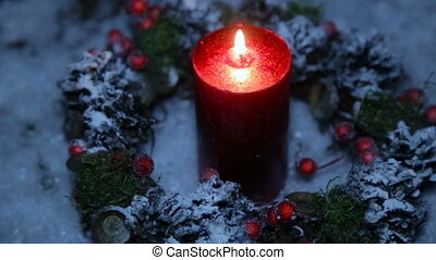 A lighted candle on Christmas night against the background...