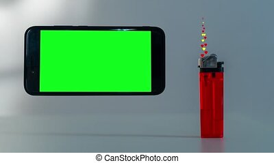 A lighter burns hearts near the smartphone with the green screen
