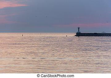 A lighthouse against the sunset sky. Beautiful peaceful seascape.