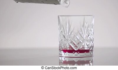 A liquid of crimson color in a glass on a white background.