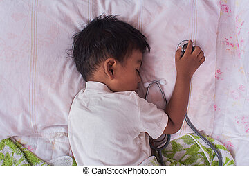 a little asian boy sleep and hand hold Stethoscope