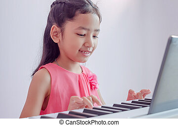 A little Asian girl playing the white keyboard with happiness