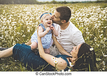 little baby girl and his family enjoying outdoors in field of daisy flowers