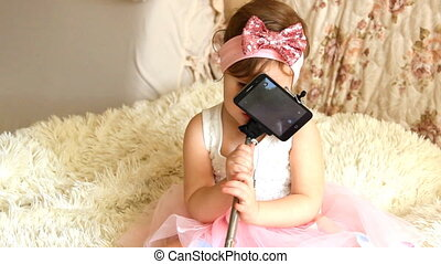 A little beautiful funny girl with takes pictures of Selfie on the phone
