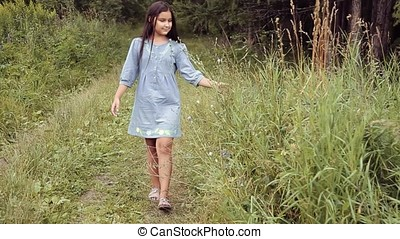 A Little beautiful girl is walking along the path in the forest and smiling sweetly