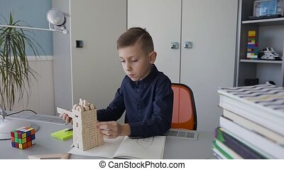 A little beautiful guy in dark blue a shirt makes measurements of the layout of a brick house that stands on his desk and makes notes in a notebook. Homework. Drawing. House