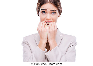 A little bit nervous about this business. Nervous young businesswoman biting her nails while standing against white background